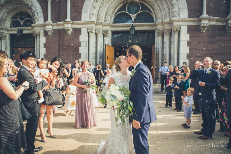 Bride and Groom kissing candidly outside the church