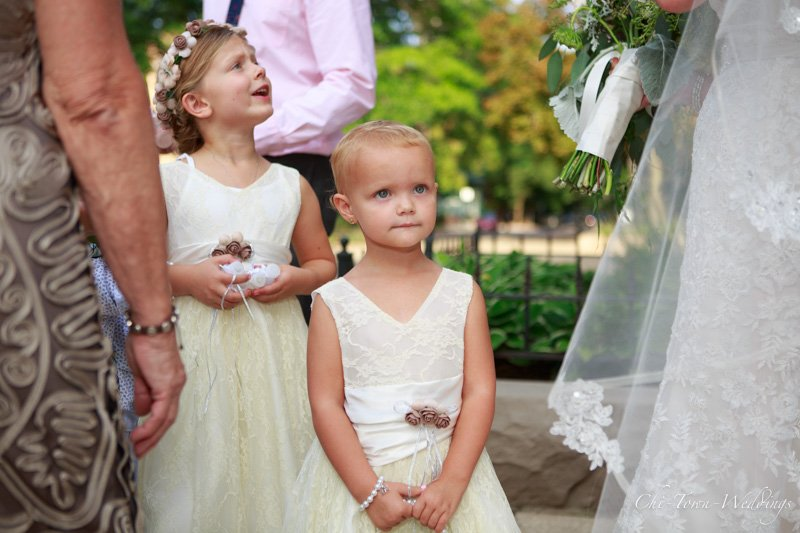 Candid of a flower girl at the wedding looking at the bride