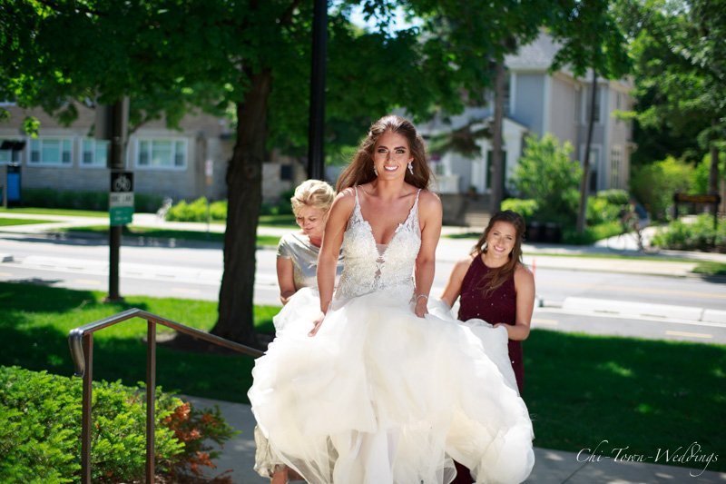 Candid bride walking up with bridesmaids helping carry dress